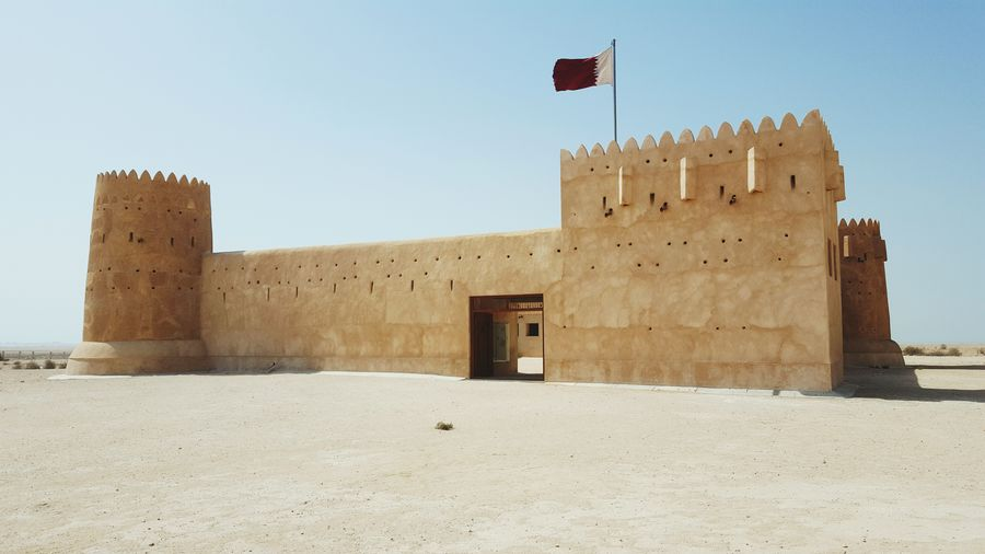 Al Architecture History Fort Travel Destinations Travel Castle Flag No People Day Qatar Doha Outdoors Architecture International Landmark Journey Zubarah Zubaraforth UNESCOheritagesite Unesco Middle East