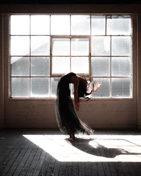 Woman with umbrella on floor in window