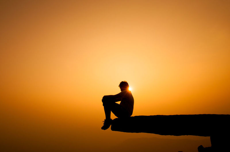 Silhouette man sitting on cliff against sky during sunset