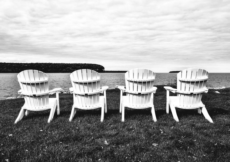 Chairs on grassy field against sky