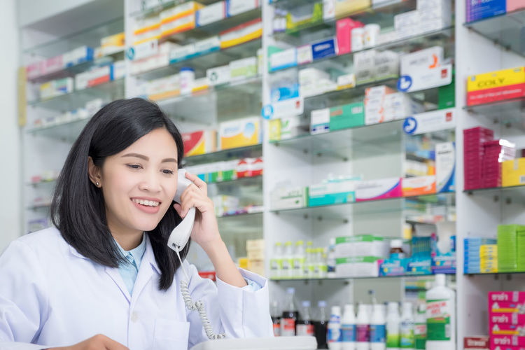 Pharmacy worker talking by phone, Attractive young smiling female at desk with telephone to ear Smiling Using Phone Communication Telephone One Person Young Adult Adult Technology Young Women Talking Pharmacy Standing Indoors  Holding Occupation Women Waist Up Front View