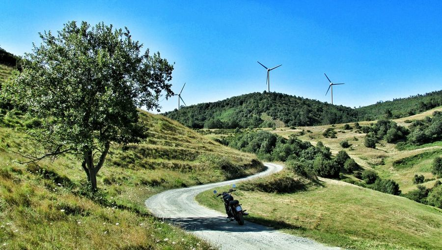 Motorbike on country road with wind turbines in background
