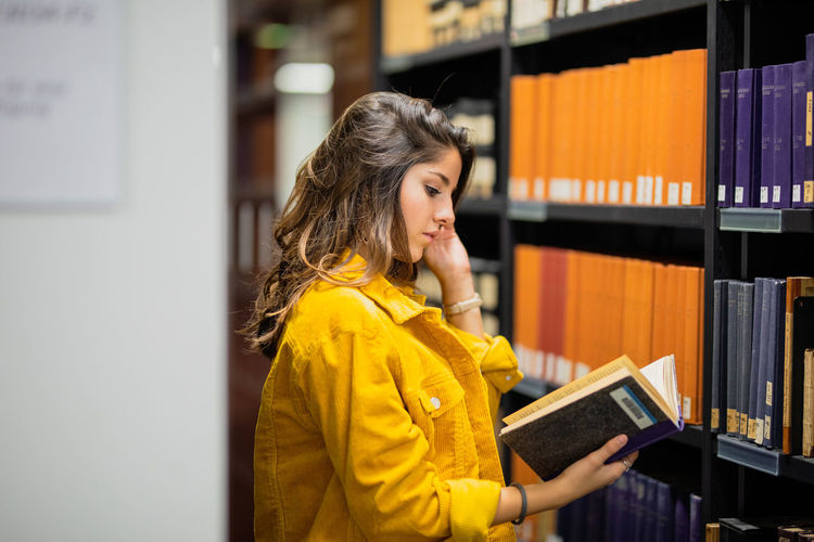 Side view of young woman reading book at library
