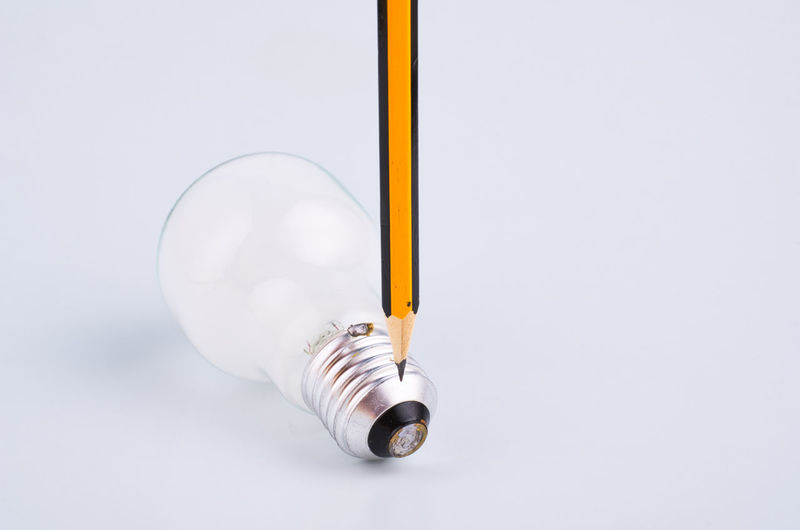 pencil and bulb over white background Studio Shot Copy Space Light Bulb Lighting Equipment Indoors  Electricity  Close-up No People White Background Cut Out Single Object Still Life Fuel And Power Generation Yellow White Color Energy Efficient Glass - Material Metal Technology Transparent Silver Colored