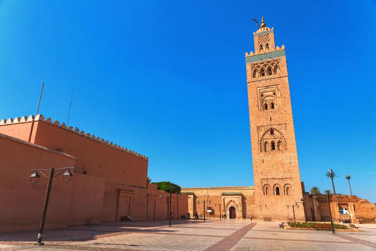 Clock tower amidst buildings against blue sky