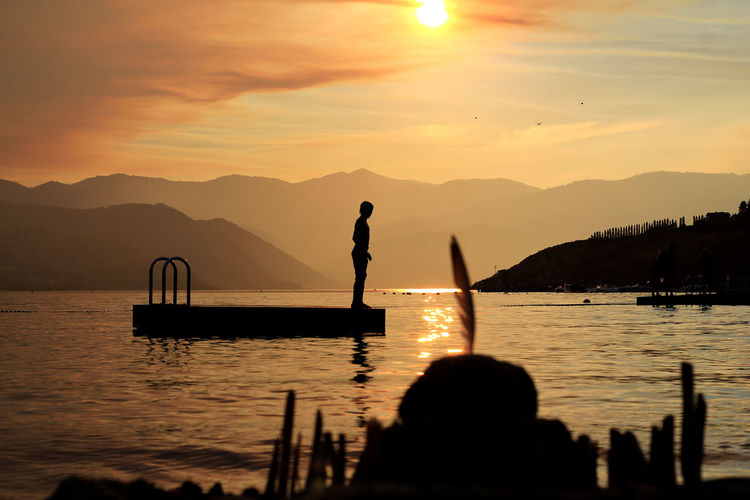 Silhouette boy standing on floating platform amidst lake