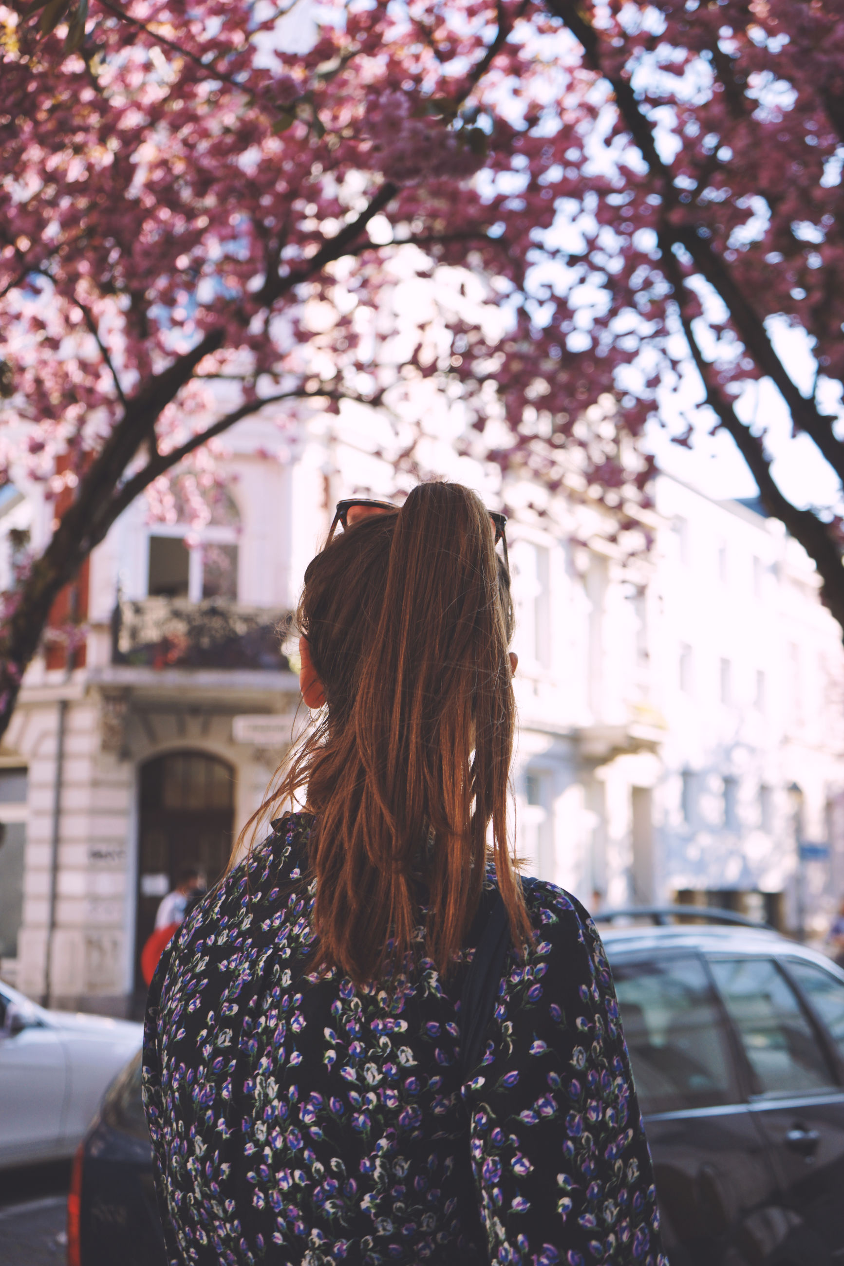 hairstyle, one person, long hair, lifestyles, tree, motor vehicle, plant, architecture, mode of transportation, real people, car, transportation, women, nature, city, day, building exterior, focus on foreground, built structure, hair, outdoors, cherry blossom, springtime, warm clothing