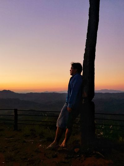 Side view of man looking at sunset