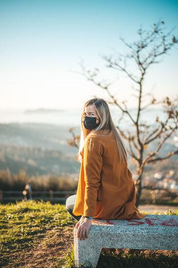 Woman wearing sunglasses on field against sky
