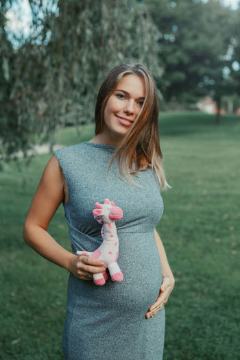 Portrait of smiling pregnant young woman holding stuffed toy by abdomen while standing on grass