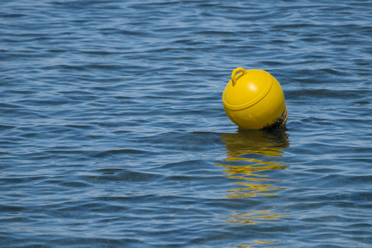 Close-up of yellow buoy floating on water