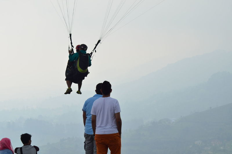 Rear view of men looking at friends paragliding