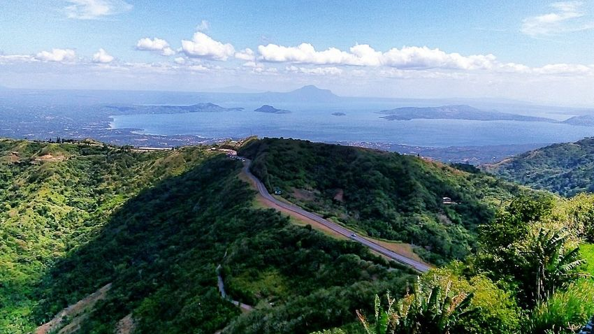"""Tagaytay & Taal Lake Skyline. Taal Volcano island (back, right) is the world's one of two """"island in a lake on an island in a lake on an island"""". A rare natural setup with a third order island. On the back and left, we can see the towns that sprung up over the centuries, living near an ever active volcano series where Taal is the major and biggest one. Eyeem Philippines Philippines Nature Travel Destinations Adventure Lake Tree Beach Water High Angle View Aerial View Sky Landscape Horizon Over Water Tranquil Scene Scenics Mountain Range Mountain Road Mountain Tranquility Summer Exploratorium The Great Outdoors - 2018 EyeEm Awards The Traveler - 2018 EyeEm Awards"""