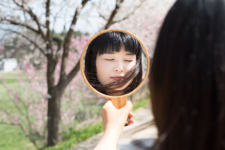 Woman with eyes closed reflecting in mirror