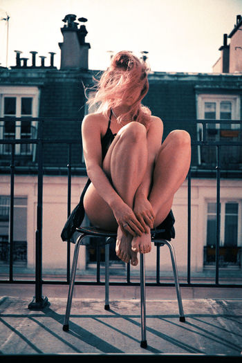 Woman sitting on chair on a balcony against sky and parisian roofs