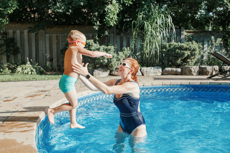 Caucasian mother training toddler son to swim in swimming pool outdoor. baby boy diving