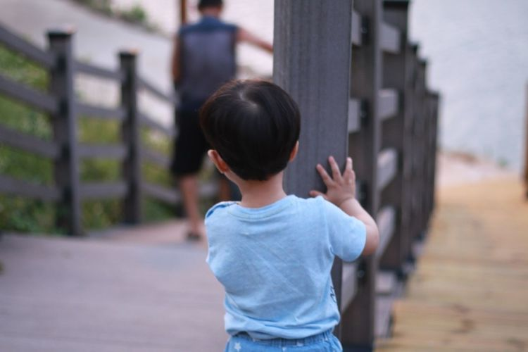 Rear view of boy looking at man walking on steps