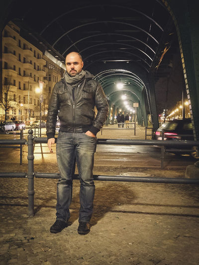 Portrait of man standing by railing on street at night