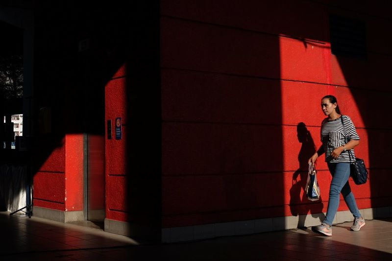 Full length of woman standing by red building