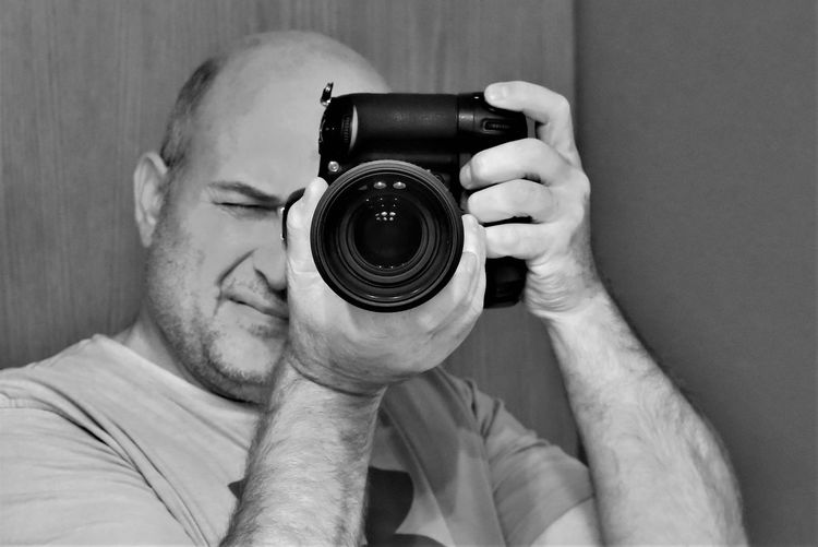 Close-up of mature man photographing with camera by wall