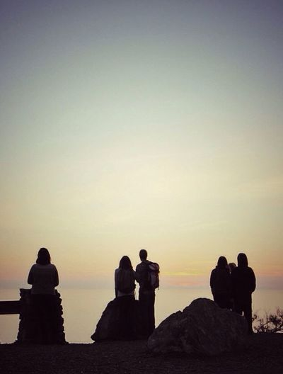 People sitting on rock at sunset