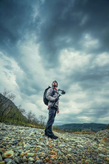 Low angle view of hiker holding camera while standing on field against cloudy sky