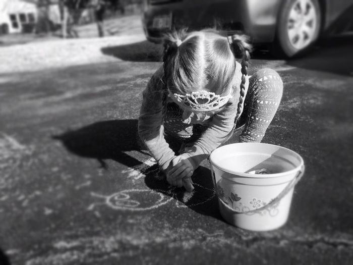 High angle view of girl drawing on street with chalk