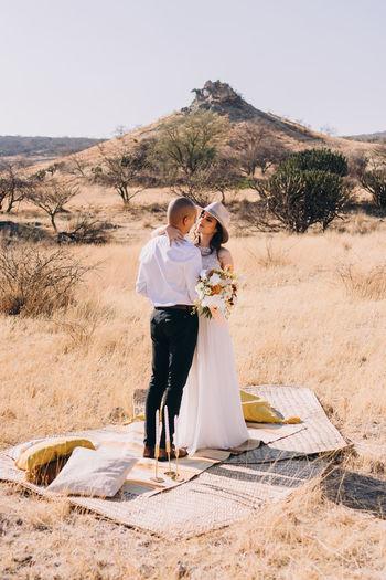 Full length of couple standing against sky