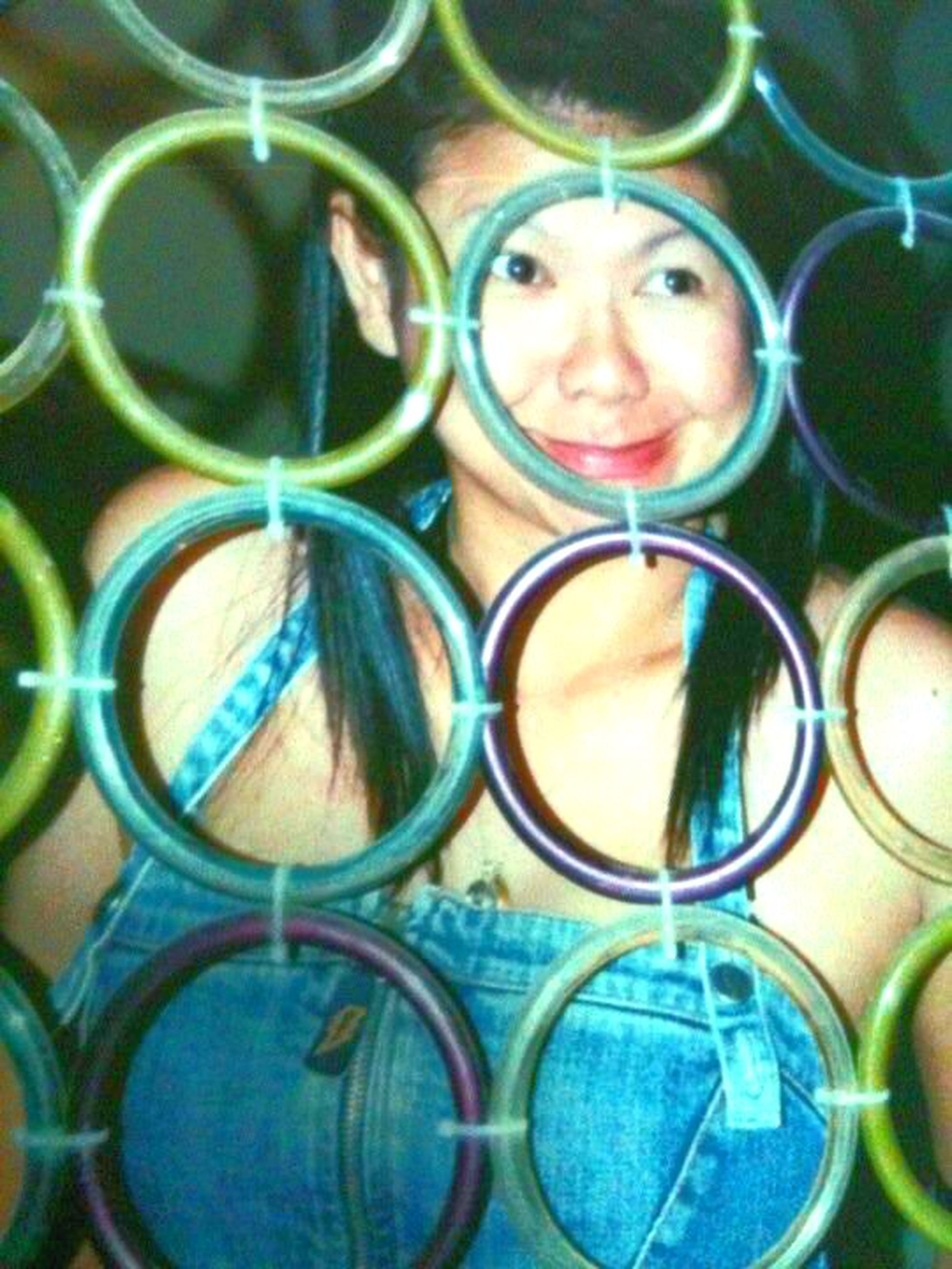 portrait, looking at camera, full frame, circle, backgrounds, pattern, protection, close-up, front view, reflection, outdoors, geometric shape, multi colored, day, blue, safety, childhood, chainlink fence