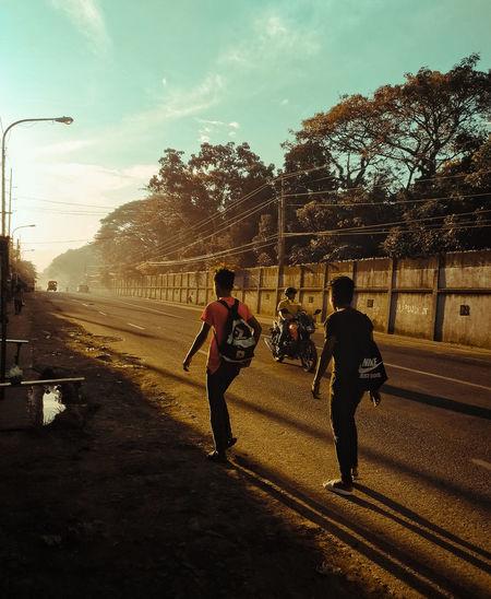 People on road against sky in city