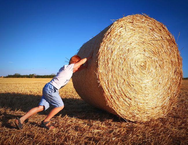 Full length of boy pushing hay bale on field against sky