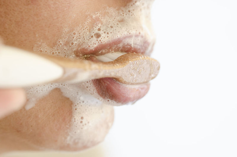 Woman cleaning her teeth with a toothbrush Adult Adults Only Beauty Cleaning Close Up Close-up Color Day Every Day Face Headshot Human Body Part Human Lips Lifestyles One Person One Woman Only Only Women Part Of Face People Side View Teeth Toothbrush Toothbrushing Toothpaste White Background
