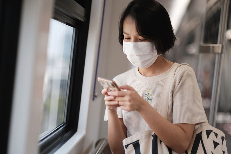 Young woman using phone by window in train