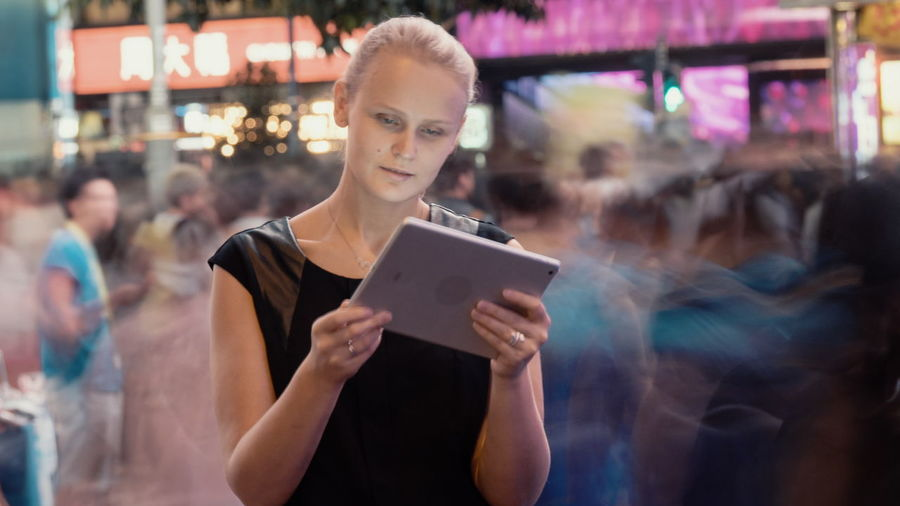 Portrait of woman holding smart phone while standing on illuminated laptop
