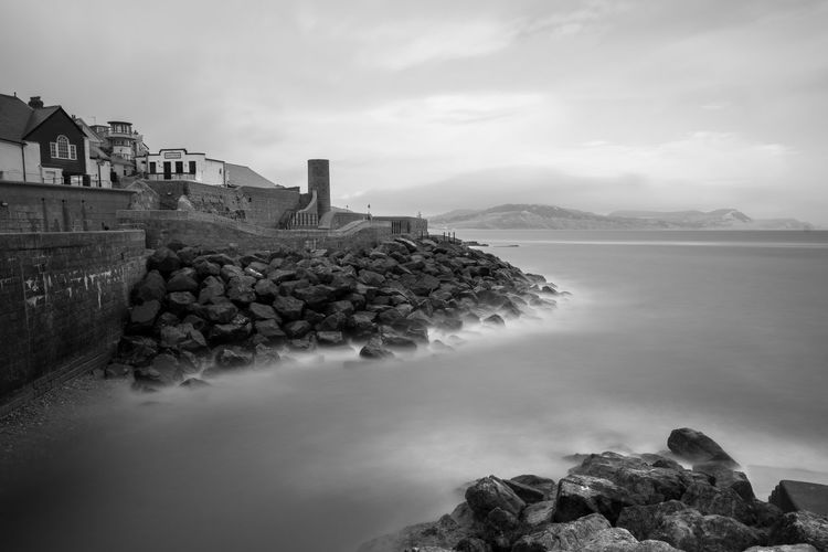 Long exposure of the sea washing up against the rocks at lyme regis in dorest