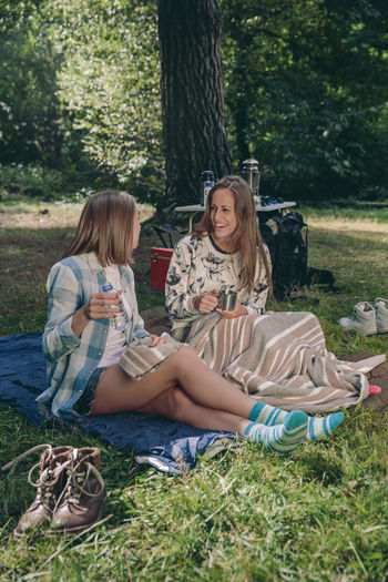 Happy young women friends laughing sitting in campsite into the forest Camping Campsite Coffee Hiking Nature Travel Trip Woman Adventure Backpack Car Caucasian Cup Equipment Female Forest Mountain Off Road Outdoors Sleeping Bag Tent Two People Vehicle Vertical Young Adult