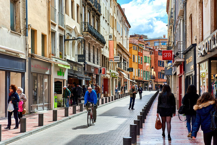 Perpignan, France - April 8, 2016: People walking in the Perpignan main commercial street in the old town. It is one of the most famous shopping street in the city, a narrow but long street with plenty of stores. Pyrenees-Orientales, France Advertisement Building Exterior City Commercial Day Editorial  European  France Languedoc-Roussillon Market Midi-Pyrenees Narrow Street Outdoors Pedestrians Walking People Perpignan Pyrénées-Orientales Roussillon Shopping Sidewalk Stores Tourists Travel Destinations Urban Walkway