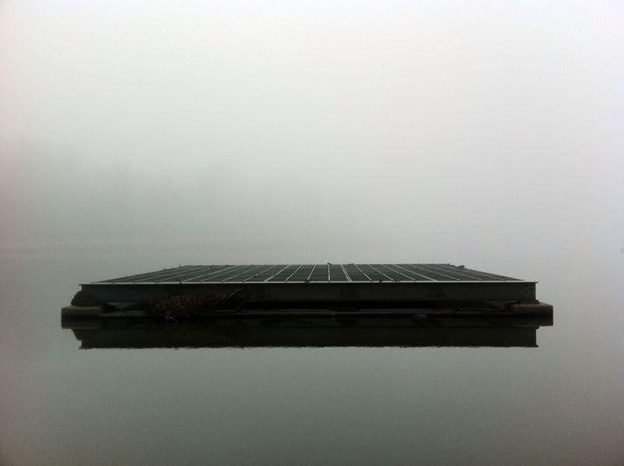 Raft in calm lake against clear sky