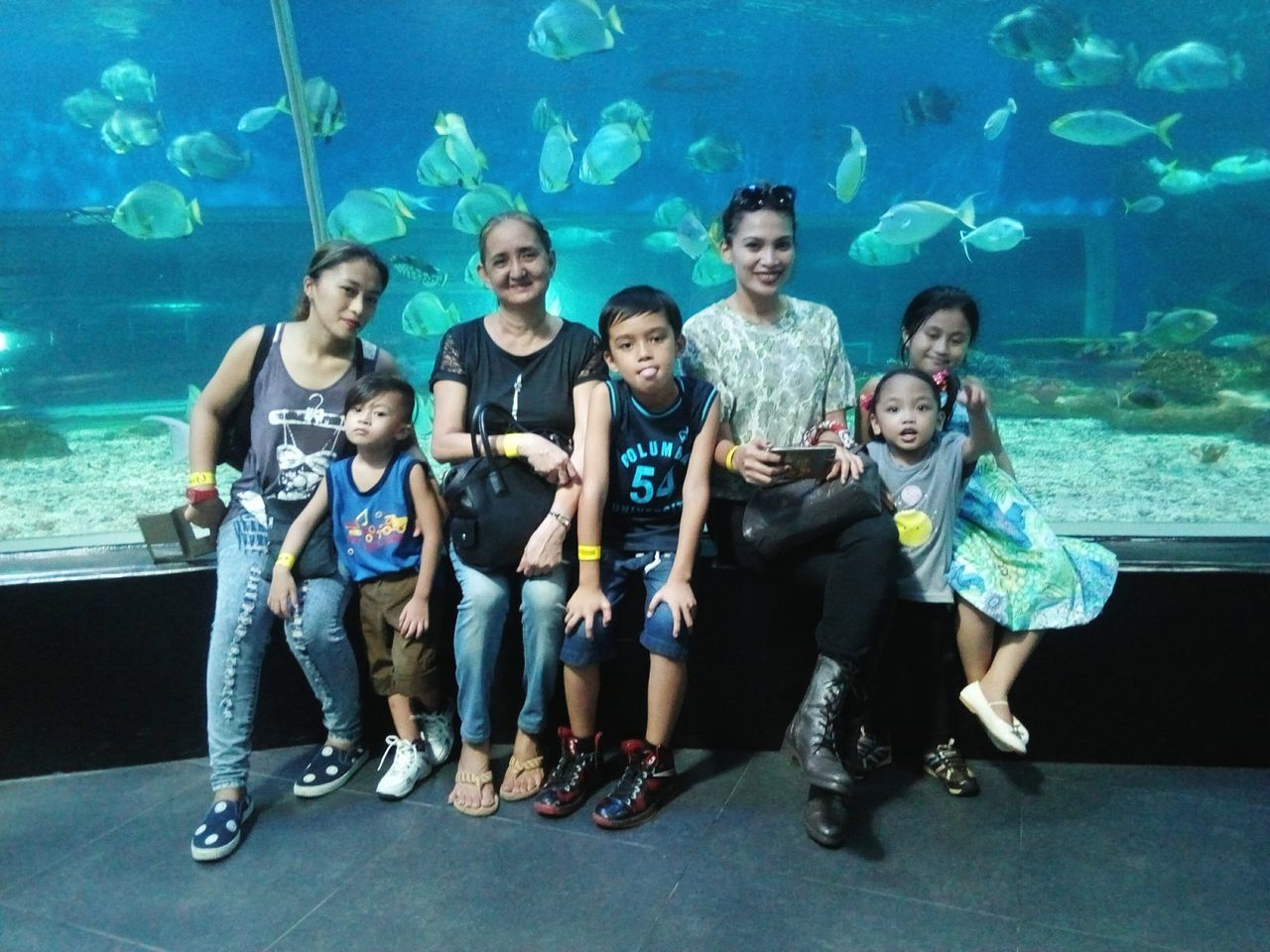 happiness, girls, smiling, casual clothing, front view, child, fun, togetherness, full length, leisure activity, aquarium, standing, enjoyment, childhood, underwater, indoors, boys, lifestyles, day, young adult, water, cheerful, women, men, portrait, people, adult