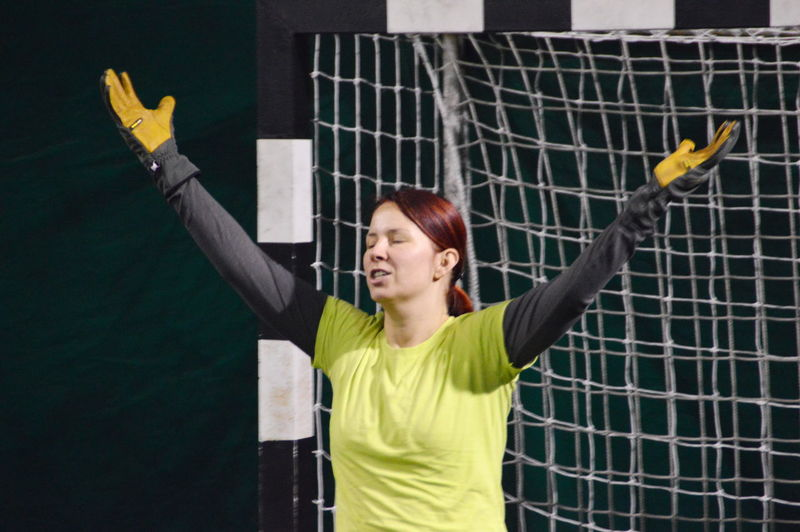 Female goalie with arms raised
