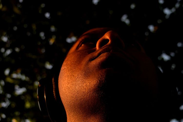 Low Angle View Of Man Listening To Music Against Trees