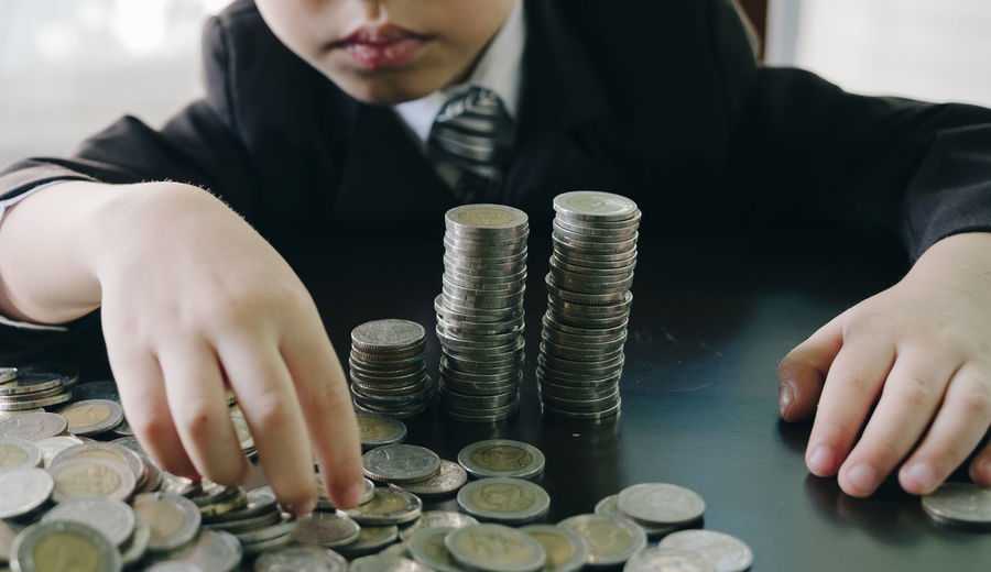 Midsection of boy in suit stacking coins on table