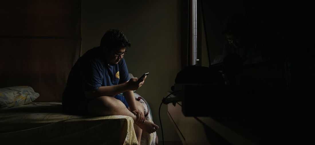 Men using mobile phone while sitting on bed at home