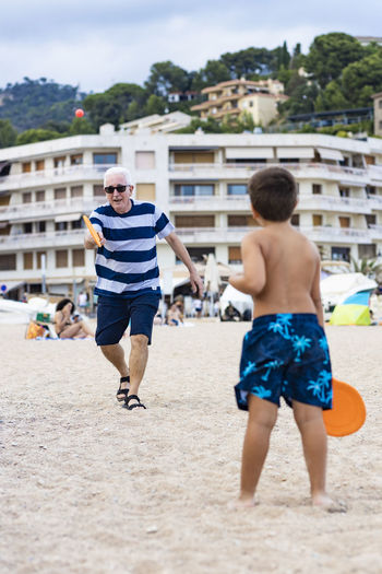 Rear view of boy playing with grandfather on beach