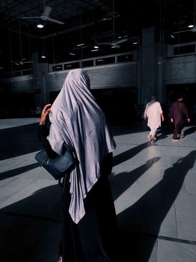 Rear view of a muslim women walking on footpath