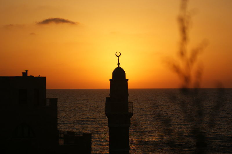 Silhouette mahmoudiya mosque minaret against sea during sunset