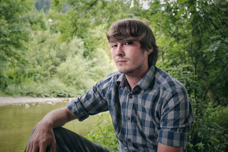 Portrait of handsome young man sitting at lakeshore against plants in forest