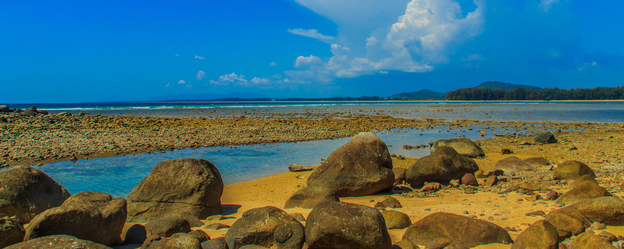 Beautiful rock stones on the beach when the sea water receded with dramatic blue sky background on the cloudy day. Rock Rocky Rocky Beach Rocky Beach Cove Rocky Beach Panoramic View Rocky Coastline Rocky Shore Beauty In Nature Blue Sky Blue Sky And Clouds Cloud - Sky Day Horizon Over Water Nature No People Outdoors Rock - Object Rock Beach Rocky Beach With Sand Rocky Landscape Scenics Sea Sky Stone Beach Stones Tranquil Scene Tranquility Water