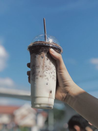 Cropped hand holding iced coffee against sky