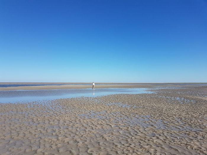 Man Walking At Beach Against Clear Blue Sky